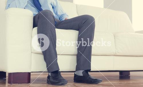 Low part of classy businessman sitting on cosy sofa