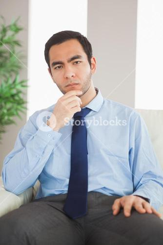 Young classy businessman thinking on cosy sofa