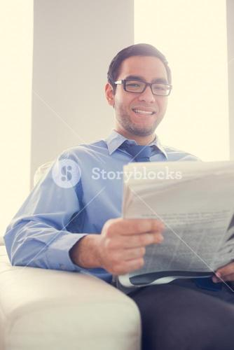 Content man looking and holding a newspaper sitting on sofa