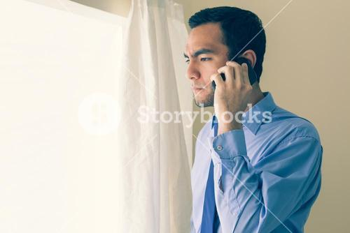Irritated man calling someone with a mobile phone and looking out the window
