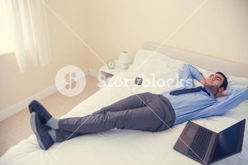 Pleased man relaxing on his bed