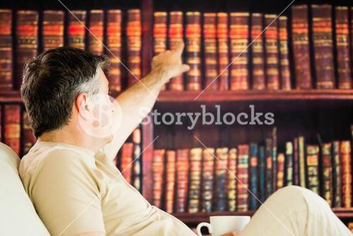 Sitting man picking a book in a reading room and drinkig coffee