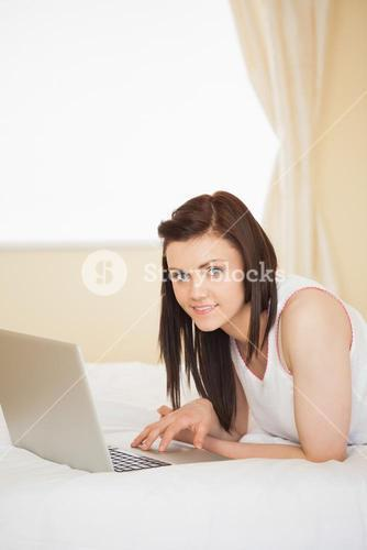 Content girl using a laptop lying on her bed