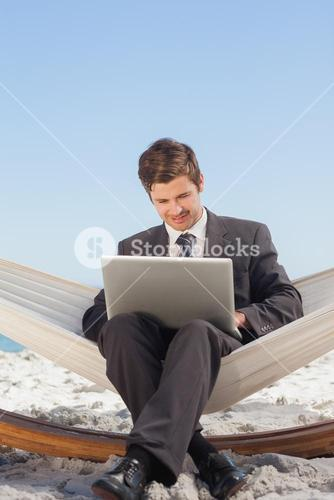 Businessman typing on his laptop in a hammock and smiling