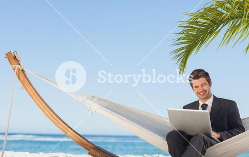 Businessman sitting in hammock using laptop looking at camera
