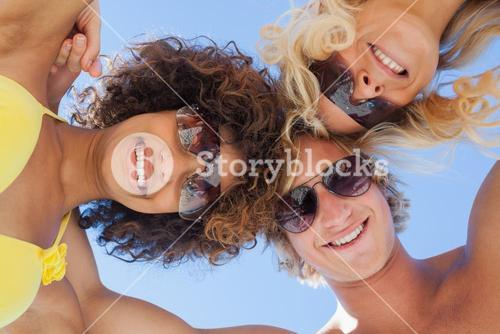 Low angle view of friends on beach wearing sunglasses