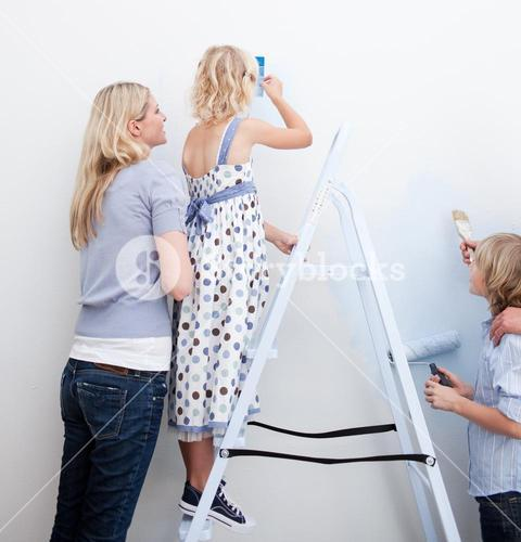 Young family paiting a room