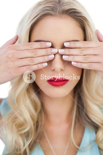 Blonde model in blue dress hidding her eyes with her hands