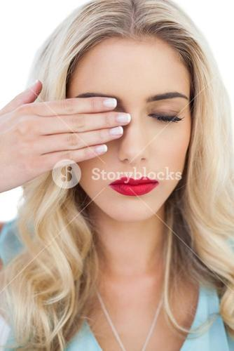 Blonde model in blue dress hidding one eye with her hand