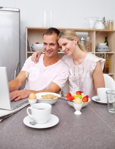 Enamored couple using a laptop while having breakfast