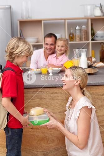 Caring mother packing the school lunch to his son