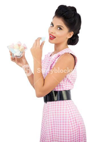 Pleased black hair model eating candies