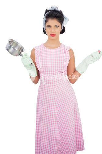 Disppointed black hair model holding a pan and wearing rubber gloves
