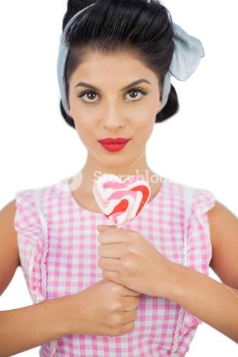 Charming black hair model holding a heart shaped lollipop