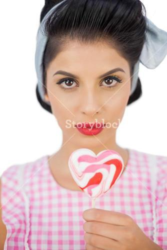 Serious black hair model holding a heart shaped lollipop