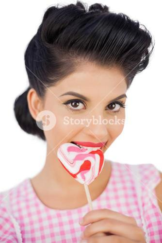 Cheerful black hair model chewing a heart shaped lollipop