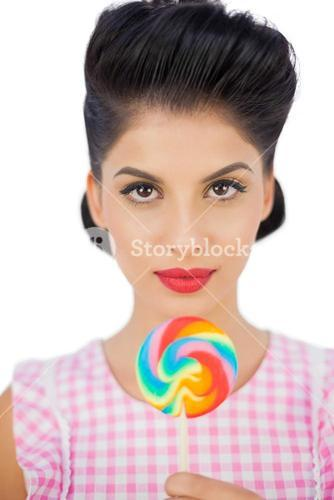 Unsmiling black hair model holding a colored lollipop