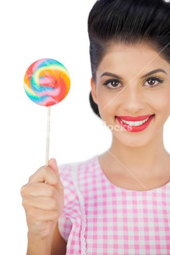 Pleased black hair model holding a colored lollipop