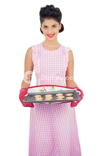 Pleased black hair model holding a baking tray of cookies