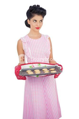 Pensive black hair model holding baking tray of cookies