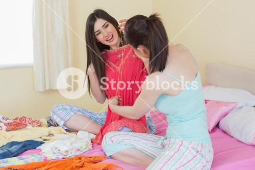 Smiling girls looking at a dress at a sleepover
