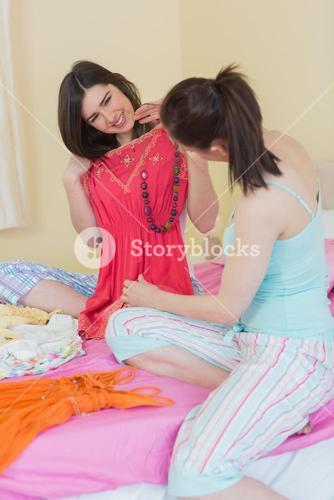Happy girls looking at a dress at a sleepover