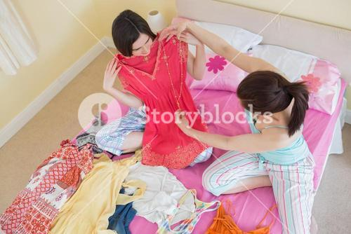 Cute girls looking at a dress at a sleepover