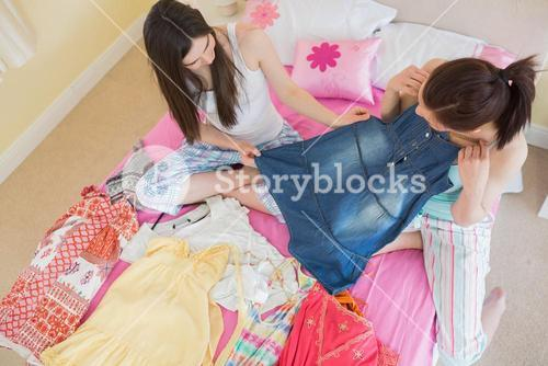 Cute girls looking at a denim dress at a sleepover