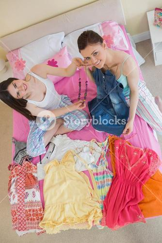 Cute girls making an outfit and looking at camera at sleepover