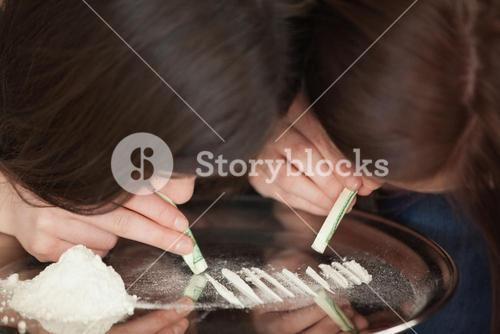 Two girls snorting an illegal white powder