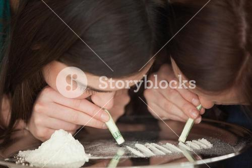 Two young girls snorting an illegal white powder