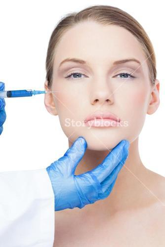 Peaceful attractive model having botox injection on the cheek