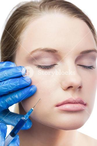 Content cute model having botox injection on the cheek