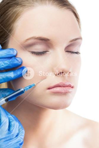 Relaxed gorgeous model having botox injection on the cheek