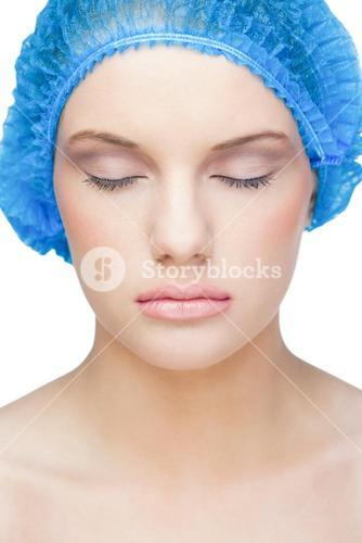Relaxed pretty model wearing blue surgical cap