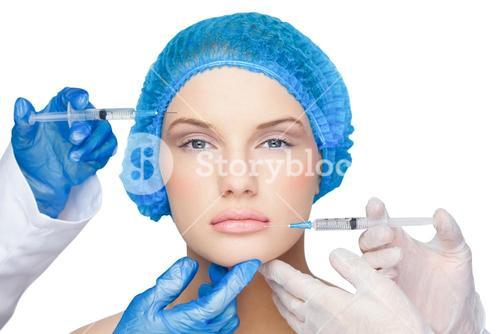 Surgeons making injection on calm blonde wearing blue surgical cap