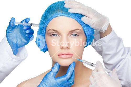 Surgeons making injection on pretty blonde wearing blue surgical cap