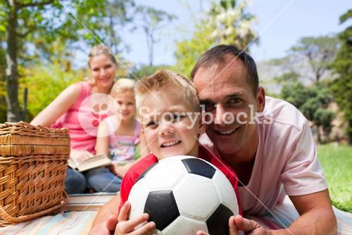 Smiling family ralaxing at a picnic