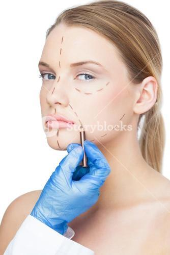 Surgeon drawing dotted lines on gorgeous patient