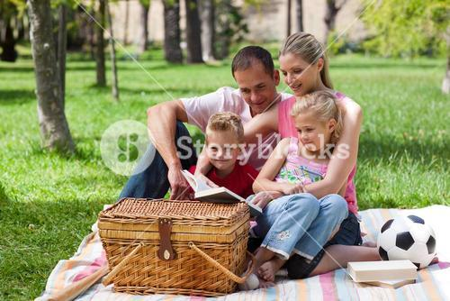 Smiling family reading while having a picnic