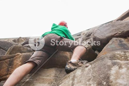 Determined man ascending a large rock face and seeing the top