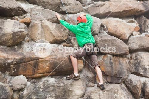 Determined man scaling a huge rock face