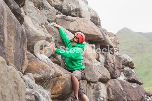 Fit man scaling a large rock face