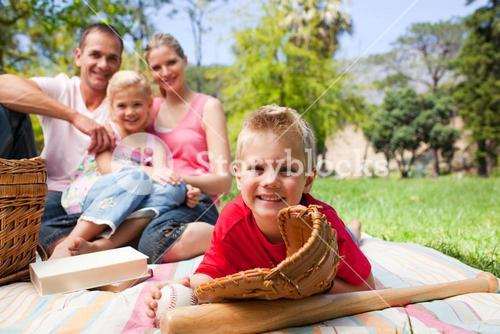 Smiling little boy wearing a baseball glove while having a picnic with his family