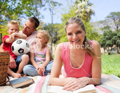 Smiling woman reading at a picnic with her family