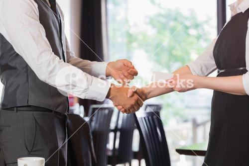 Business team shaking hands and swapping card