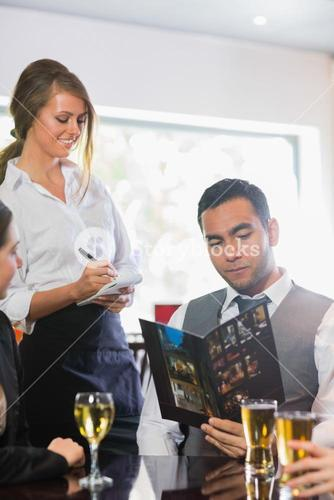 Businessman ordering a dinner from smiling waitress