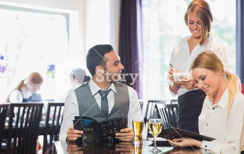 Business people reading menu and ordering