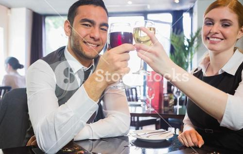 Smiling business partners clinking wine glasses looking at camera