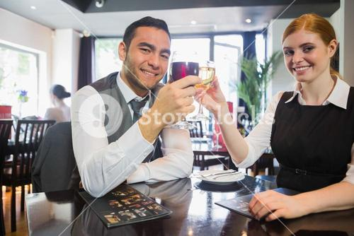 Happy business partners clinking wine glasses smiling at camera